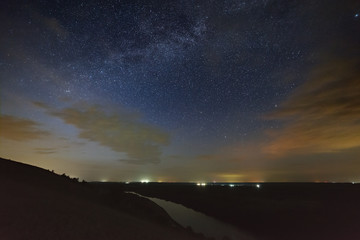Galaxy Milky Way with clouds in the night sky against the background of the river.