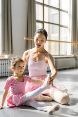 Female ballet instructor teaching girl in ballet studio