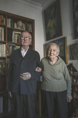 Portrait of old couple standing on artistic studio in home