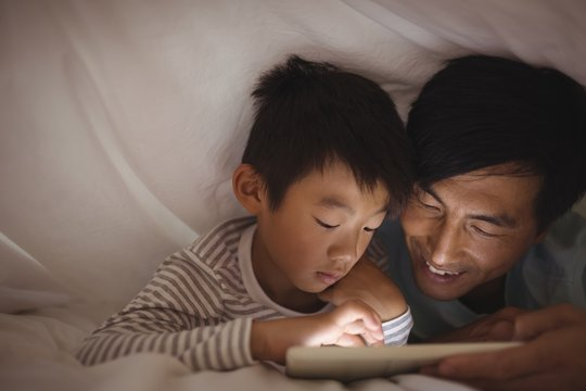 Father and son using digital tablet under blanket in bedroom