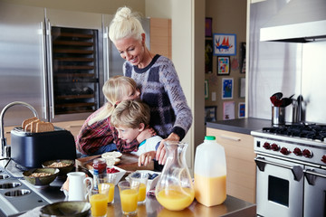 Mom and kids making breakfast in the morning in the kitchen