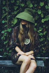 Girl in the garden wearing a shirtdress and a giant cloche hat
