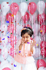 Cute little girl celebrating with confetti at her birthday party