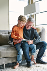 Father and son looking at digital tablet in on sofa in living room