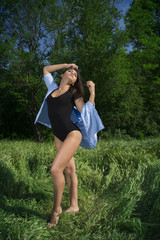 Fit young girl in bodysuit posing in a grass field