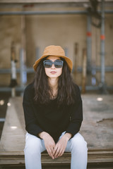 portrait of real young woman with hat and sunglasses