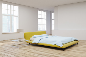 Yellow bed, wooden floor corner view