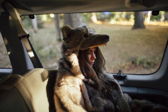 Tired brunette girl sleeps in the passenger seat of a van nestled in her wolf costume