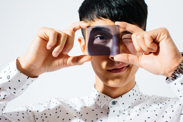 Portrait of an asian man looking through purple glass