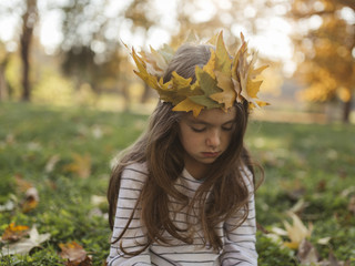 Girl with autumn leafs on her head