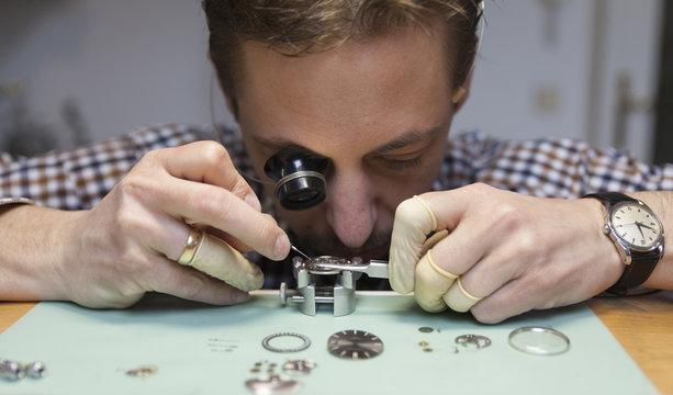Clockmaker working in workshop