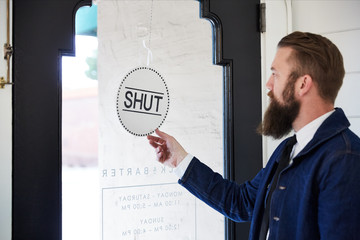 Millennial small business owner turning open/close sign in artisan retail store