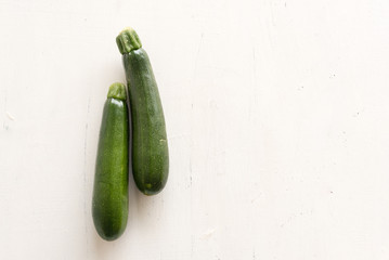 High angle view of two zucchini on rustic white background with copy space to right