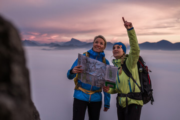 two female hiker making a plan with a hiking map in alpine scenery