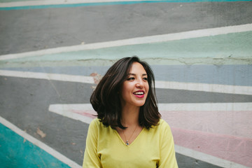 Smiling Uzbek woman with a brightly painted wall behind her