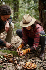 Couple mushroom foraging in the forest