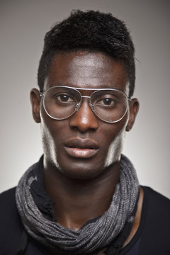 A real african man with retro glasses over grey background