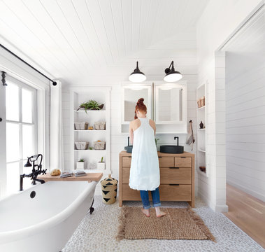 Woman washing hands in bathroom in rustic modern farmhouse