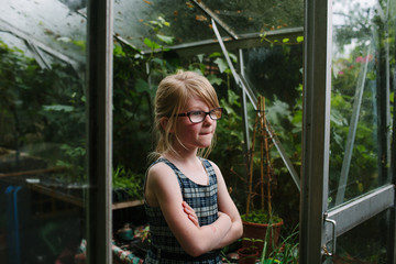 Young girl stands thoughtfully at the entrance to a garden glasshouse