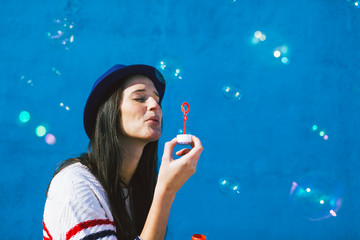 Young woman blowing soap bubbles on blue background