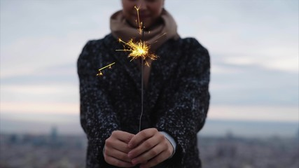 Smiling woman holding a sparkler above city in winter