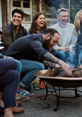 Group of friends and family relaxing around a fire pit at a farm