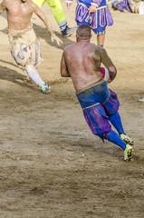 Calciante in azione mentre corre con la palla durante la partita di calcio storico fiorentino