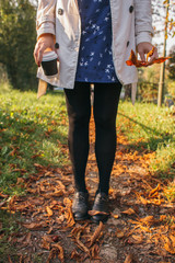 Trendy girl stands in colorful autumn leaves