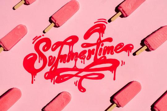 "Handwritten word ""Summertime"" with arranged pink ice creams around it"