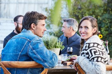 Portrait of couple with group of friends enjoying a Farm To Table Dinner Party in backyard