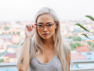 Young asian female model wears glasses on rooftop