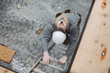 Carpenter man climbing down ladder at construction site