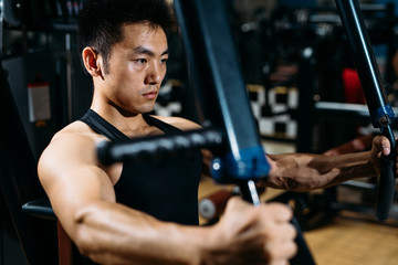 Man doing chest exercises with a fitness machine