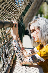 portrait of urban young female in city next to chain link fence