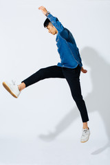 Jumping stylish asian man over white background