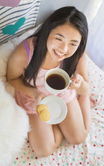 Lifestyle angled portrait of a beautiful young happy Asian woman holding a cup of hot tea or coffee in bed in the morning.  relaxing, resting, looking up, thinking happy healthy thoughts.