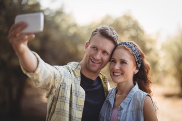 Cheerful young couple taking selfie at olive farm