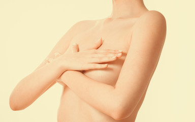 Woman covering her breast with hands