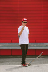 teenager with skateboard in front of red background showing his middle finger