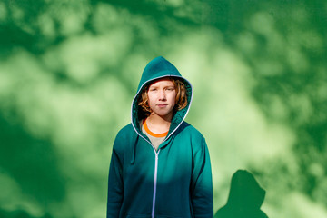 Young boy standing against the green wall