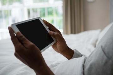 Mid section of senior man holding digital tablet on bed