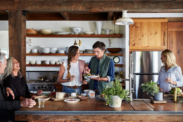 Family and friends cooking together in rustic farmhouse kitchen