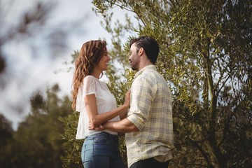 Loving young couple standing by trees at farm