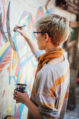 Young woman drawing a colorful mural