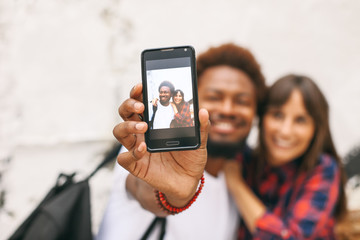 Two friends making a selfie on urban city