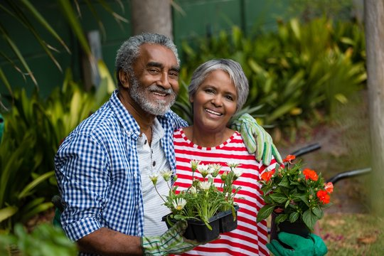 Portrait of smiling senior couple standing together in backyard