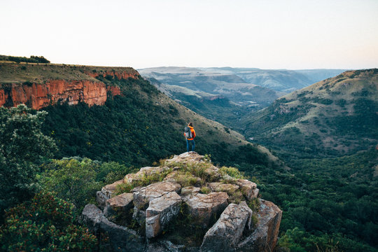 Hiker on a rocky outcrop overlooking a scenic valley