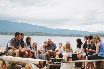 Extended family group hanging out around campfire near lake