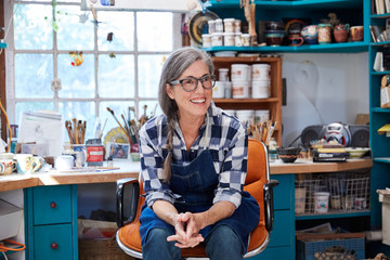 Portrait of senior woman with grey hair inside her pottery studio