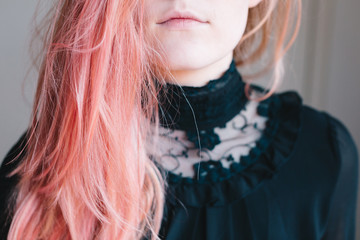 Anonymous young woman with pink hair, wearing a high collared black lace shirt